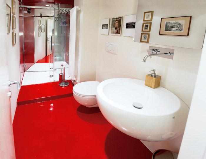 badezimmer mit einem roten boden und einem weißen waschbecken und weißen wänden mit bildern