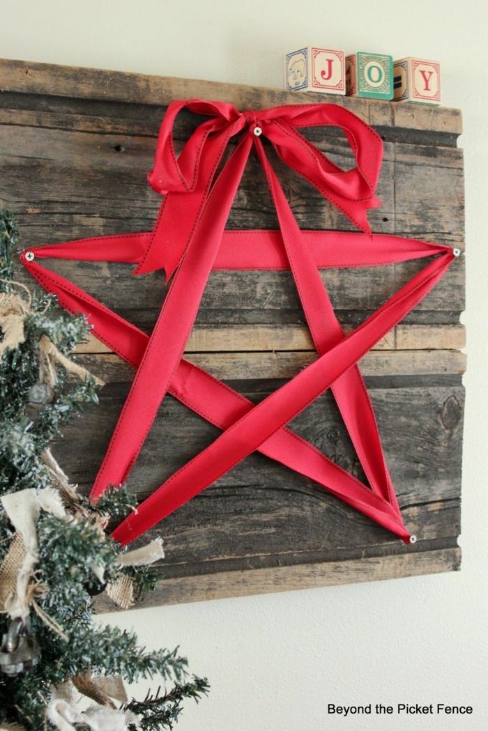 ein roter Stern aus einer Schleife, viele Nagel auf einem Brett, Bastelideen Weihnachten, neben Weihnachtsbaum