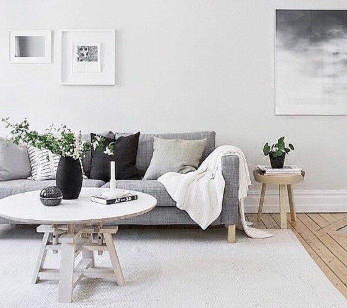 ein graues Sofa, Wohnzimmer streichen Grau Weiß, weißer Teppich, schwarze Vase mit weißen Blumen