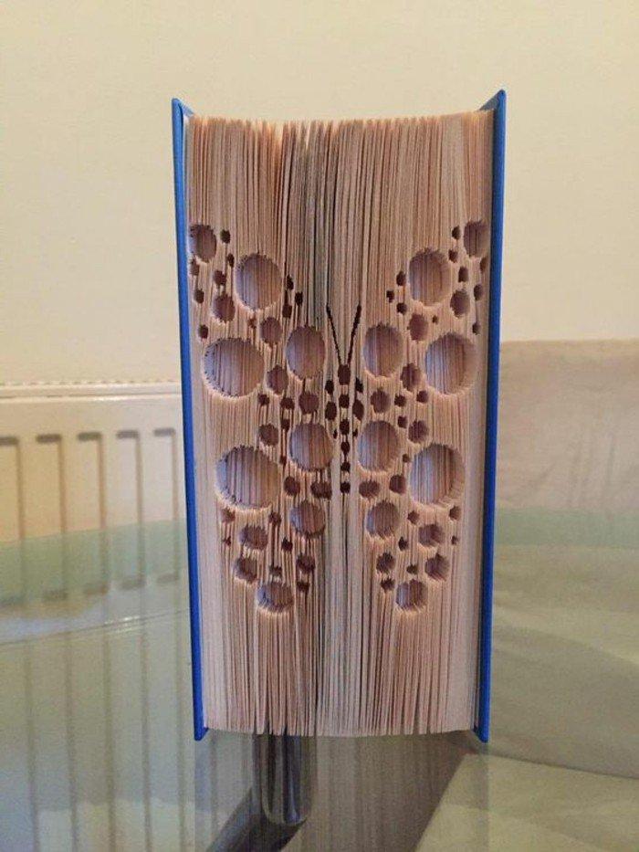 ein Schmetterling mit runden Kreisen an den Flügeln, Origami Buch mit blauem Umschlag