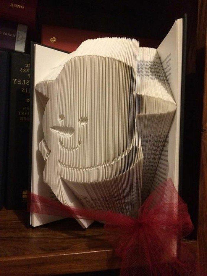 ein Schneemann mit Hut und einen Schal, eine Karotennase, Origami Buch mit roter Schleife