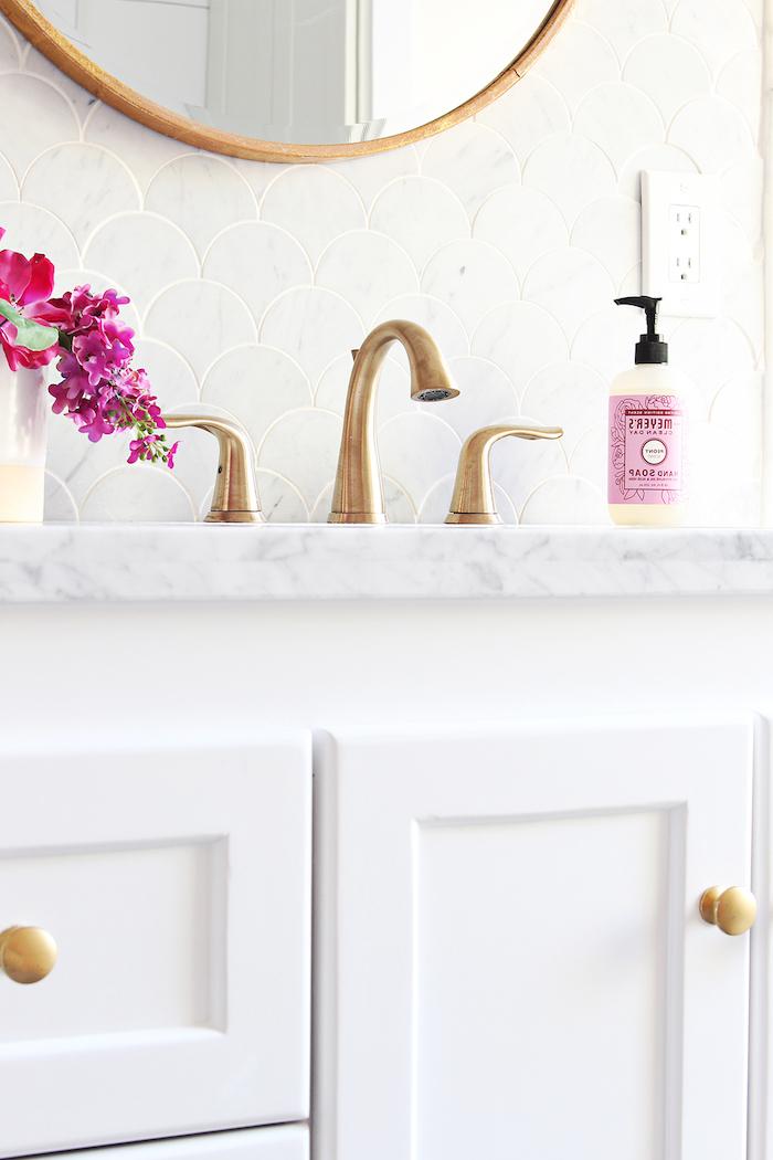 badezimmer mit einem weißen waschbecken und eiem spiegel, vase mit kleinen violetten und roten blumen
