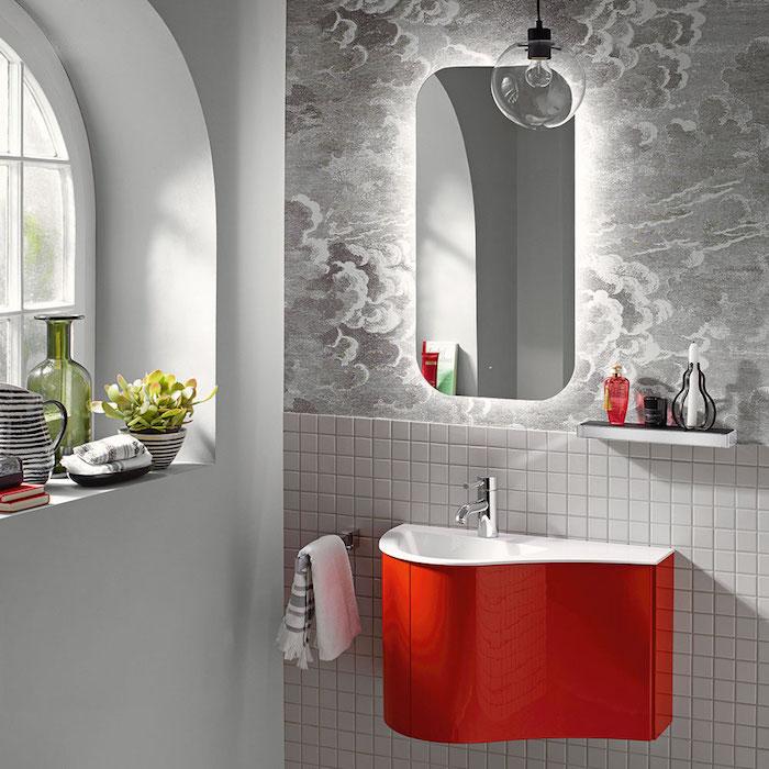 kleines rotes waschbecken und ein großer spoegel im badezimmer mot einem kleinen fenster und vase mit blumen