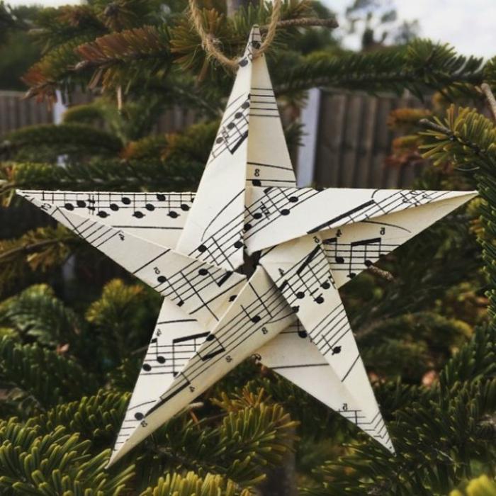 ein Stern aus Altpapier mit Noten versehen, von einem Seil gehängt, Weihnachtssterne falten
