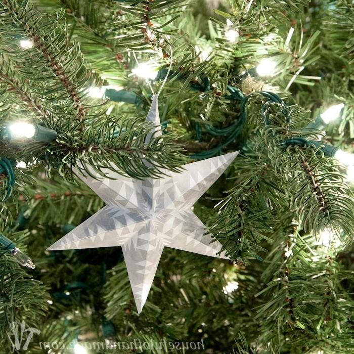 Weihnachtssterne falten, ein Stern am Weihnachtsbaum, zwischen Lichterketten, grauer Stern