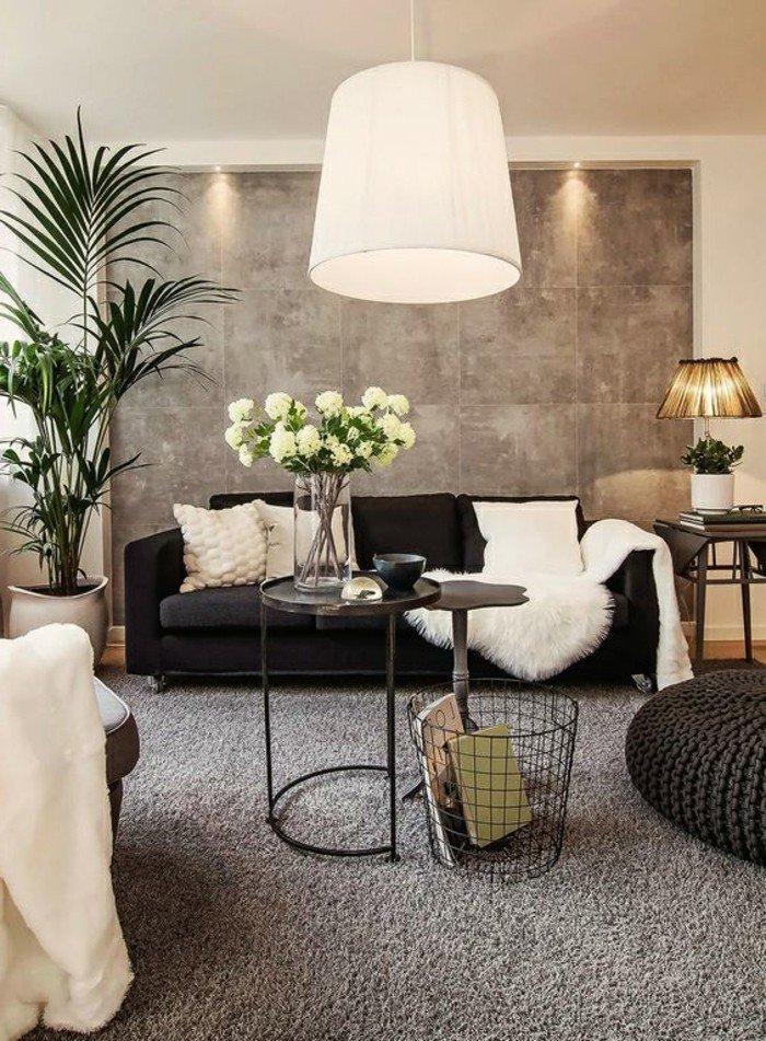 braune Wände, schwarzes Sofa, weiße Kissen, ein runder Tisch mit Glasvase voller weiße Blumen, Wohnzimmer Ideen Grau Weiß