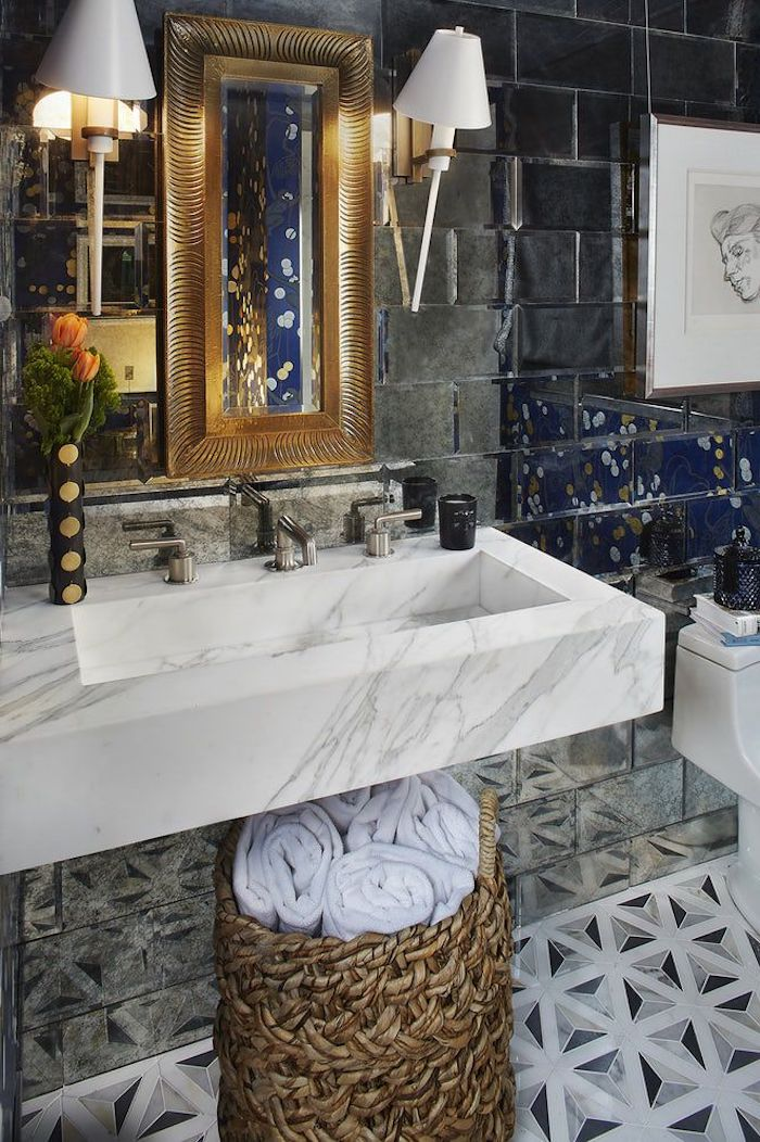 kleiner spiegel und weiße badezimmer lampen und ein weißes waschbecken im badezimmer, eine wand aus vielen blauen fliesen