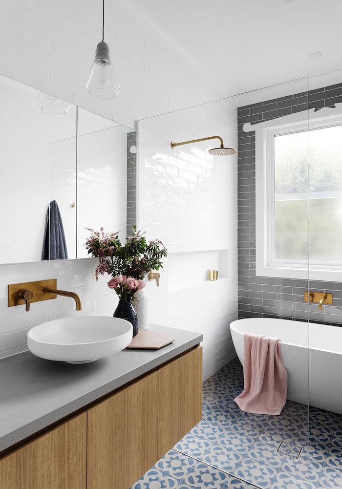 eine weiße freistehende badewanne im badezimmer mit einem wei0en waschbecken und eine vase mit violetten blumen und grünen blättern und ein spiegel