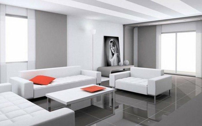 Wohnzimmer in Grau Weiß, weiße Wohnzimmermöbel, grauer Boden, rote Kissen, ein Wandbild