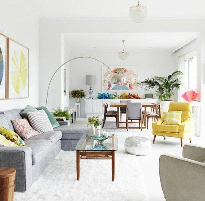 ein buntes Zimmer, graues Sofa, weißer Teppich, gelber Sessel, ein Tischlein aus Glas, Kristalllampenschirm