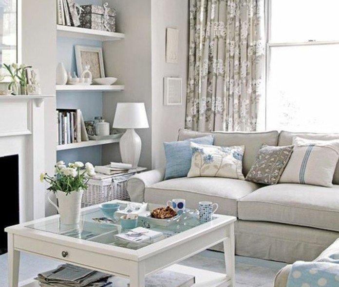 ein gläserner Tisch in weißer Farbe, ein graues Sofa, hellblaue Kissen, Wohnzimmer Ideen Weiß Grau