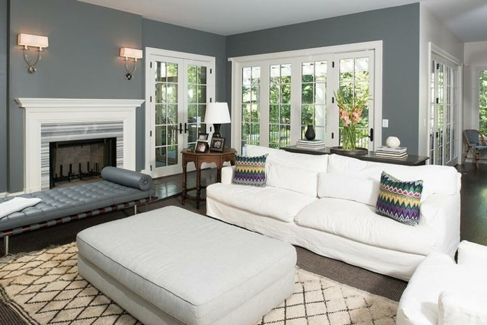 ein weißes Sofa mit zwei bunten Kissen, brauner Teppich, ein Kamin mit zwei Lampen darüber, Wohnzimmer Ideen Weiß Grau