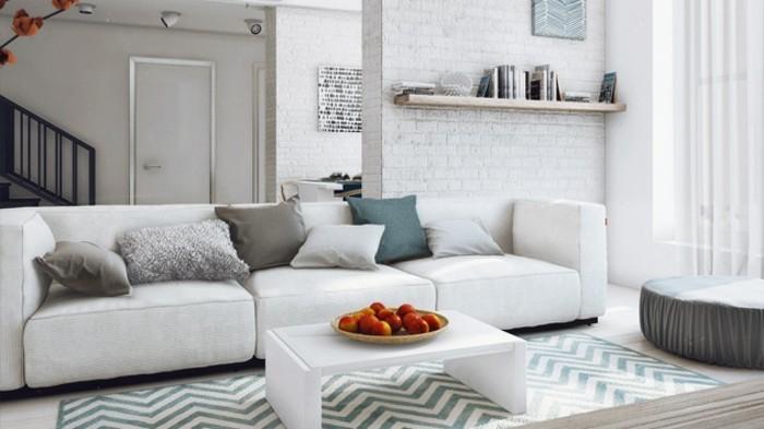 ein Regal mit Büchern, ein weiße Couch mit bunten Kissen, ein weißer Tisch, bunter Teppich, Wohnzimmer Ideen Weiß Grau