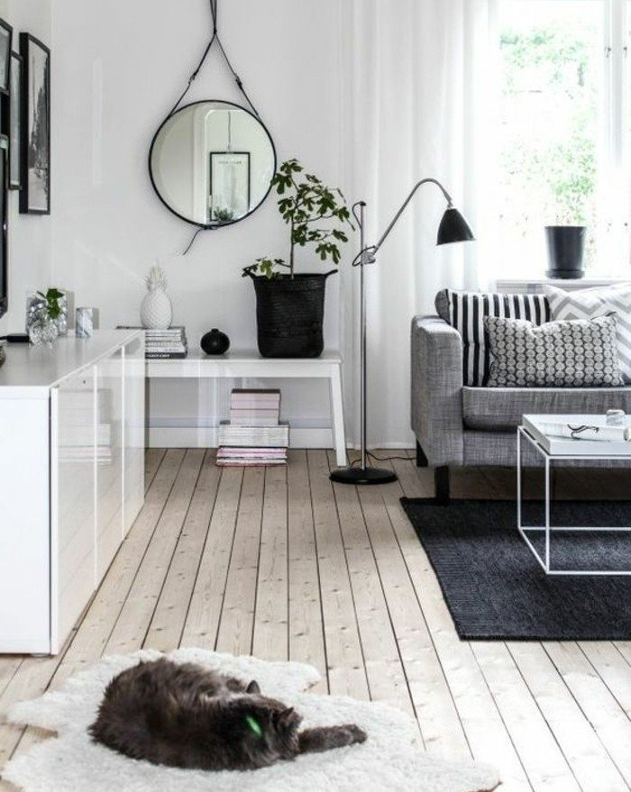 ein schwarzer Teppich, ein graues Sofa, Laminatboden, ein runder Spiegel, Wohnzimmer Ideen Weiß Grau