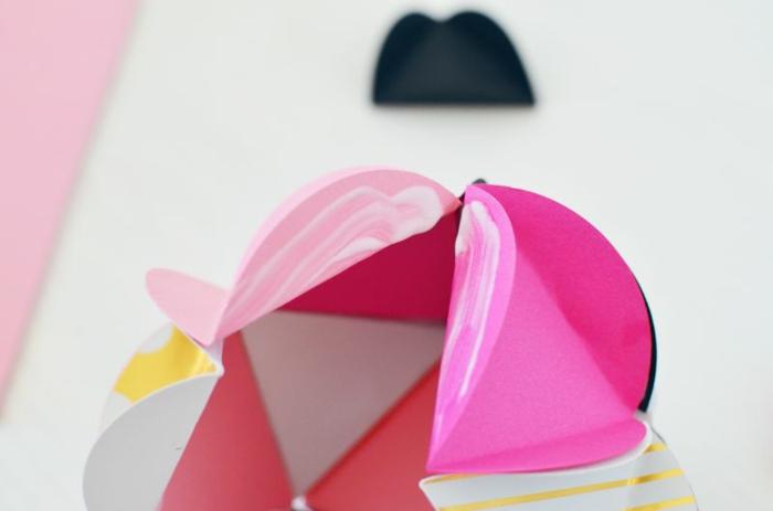 tragen Sie Klebstoff auf die Klappen auf, damit Sie rosa Weihnachtskugeln gestalten