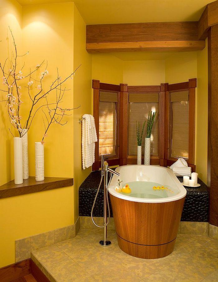 badezimmer mit einer freistehende badewanne aus holz und drei weiße vasen mit ästen