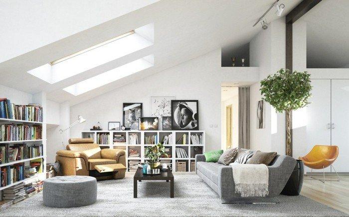 Wohnzimmer Weiß Grau, ein graues Sofa, Bücherregale in weißer Farbe, grauer Teppich in einer Dachwohnung