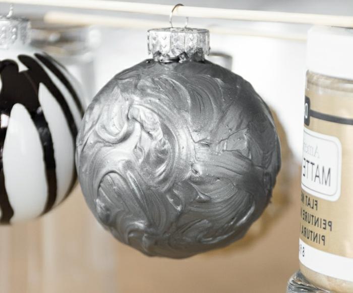 silberfarbene Kugel, die auf einem Stock trocknet, Weihnachtskugeln basteln, die bildschön aussehen