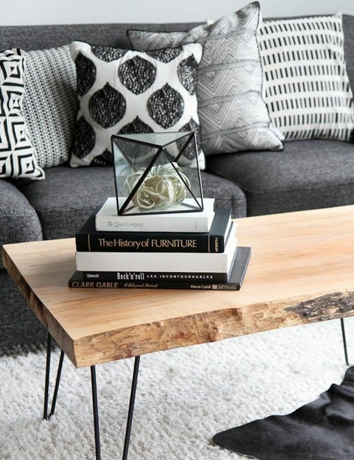 ein graues Sofa, schwarz weiße Kissen, Wohnzimmer Grau Weiß, weißer Teppich, darüber Tisch aus Holz