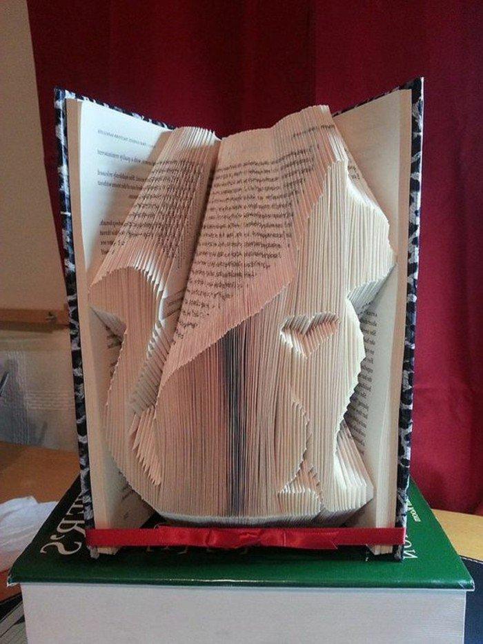 eine Katze aus Papier mit einem kleinen Herz in dem Buch geschnitzt, Buchfalttechnik