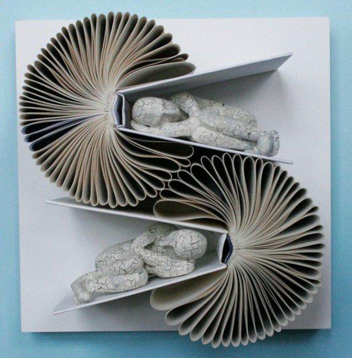 zwei Bücher, wie Blumen gefaltet, zwei Skulpturen von schlaffenden Menschen, Buchfaltkunst
