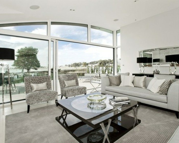 eine Wohnung mit Glaswand, ein graues Sofa, bunte Sessel und ein gläsernem Tisch, Wohnzimmer Grau Weiß