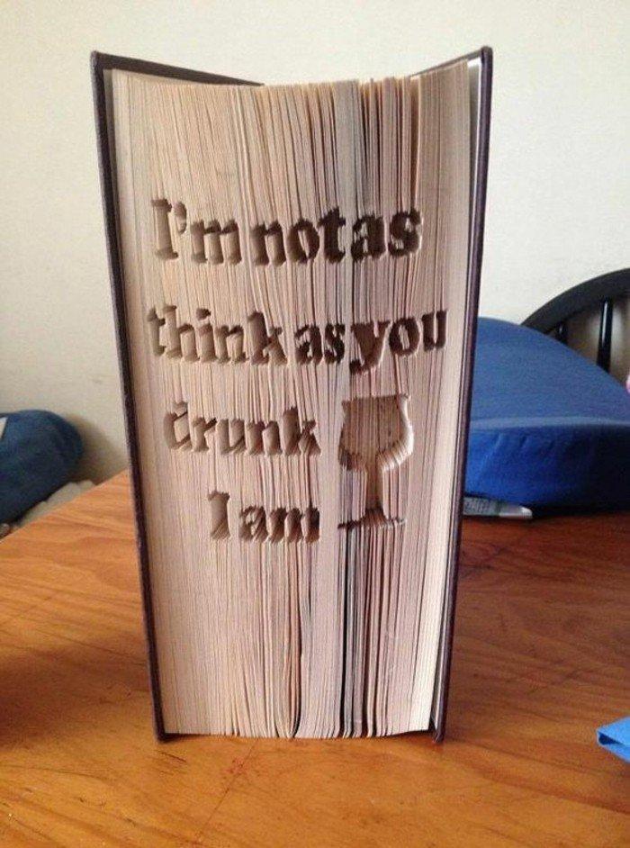 eine Botschaft und ein Glas Wein, Ein Zitat aus dem Buch, Buchseiten falten, schwarzer Umschlag
