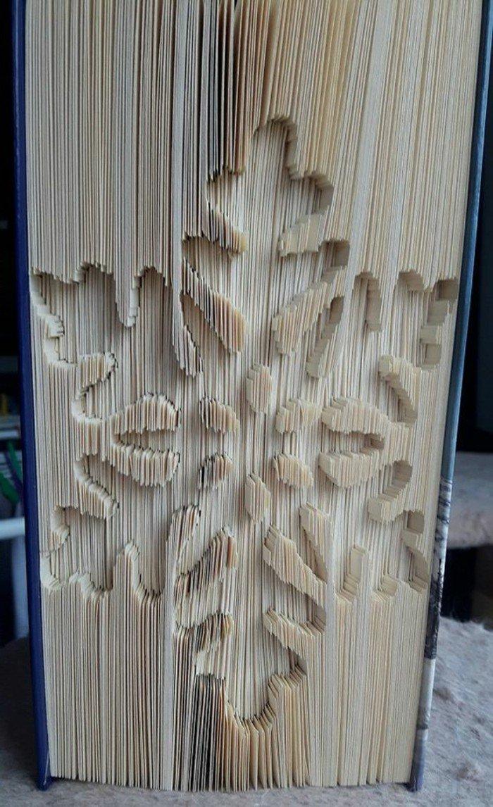 eine Schneeflocke mit sechs Spitzen, in einem dicken Buch geschnitzt, Buchseiten falten