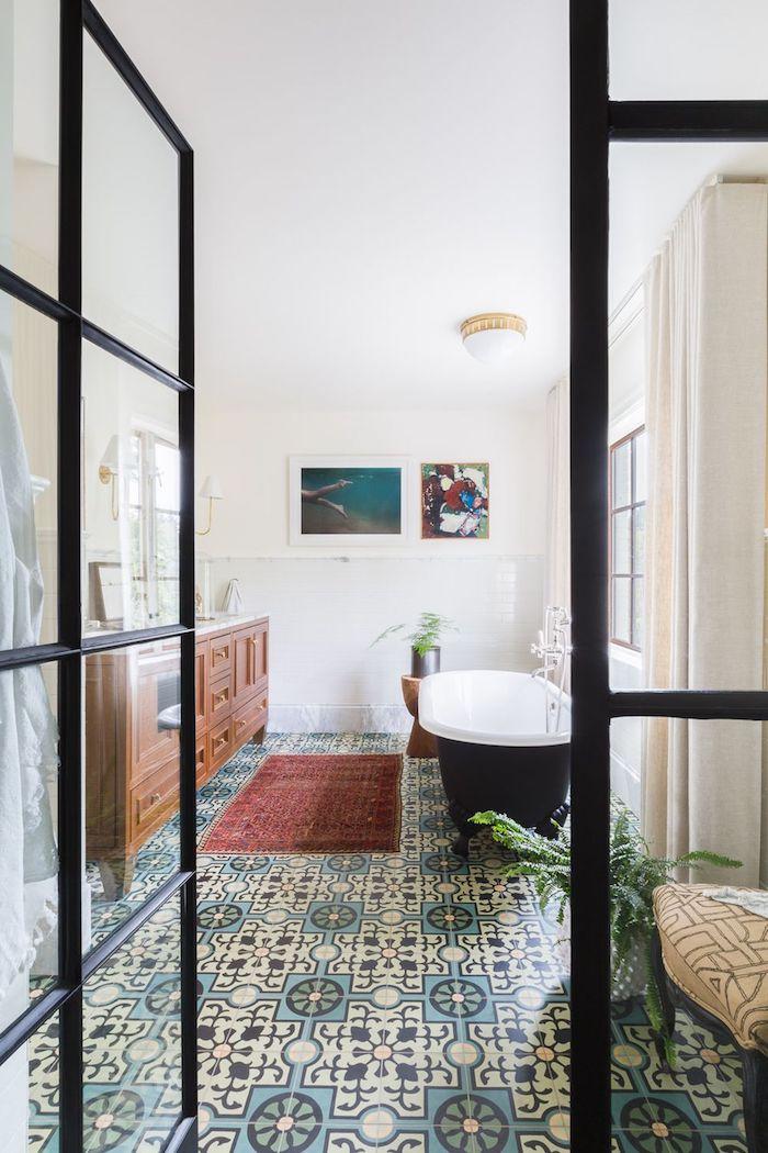 badezimmer mit einer kleinen schwarzen freistehenden badewanne und mit weißen wänden und weißen badezimmer lampen, kleiner roter badezimmer teppich