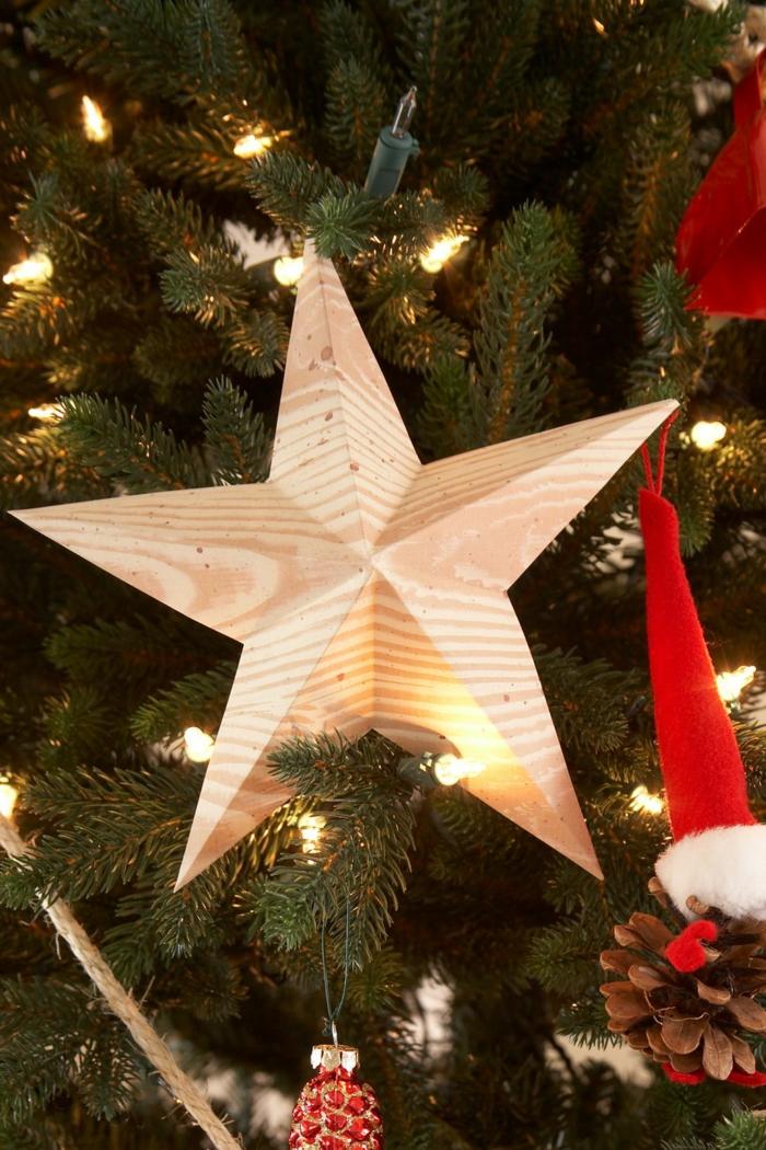 ein Stern aus Holz an dem Tannenbaum, eine Lichterkette, kleine Dekorationen, Bastelideen Weihnachten