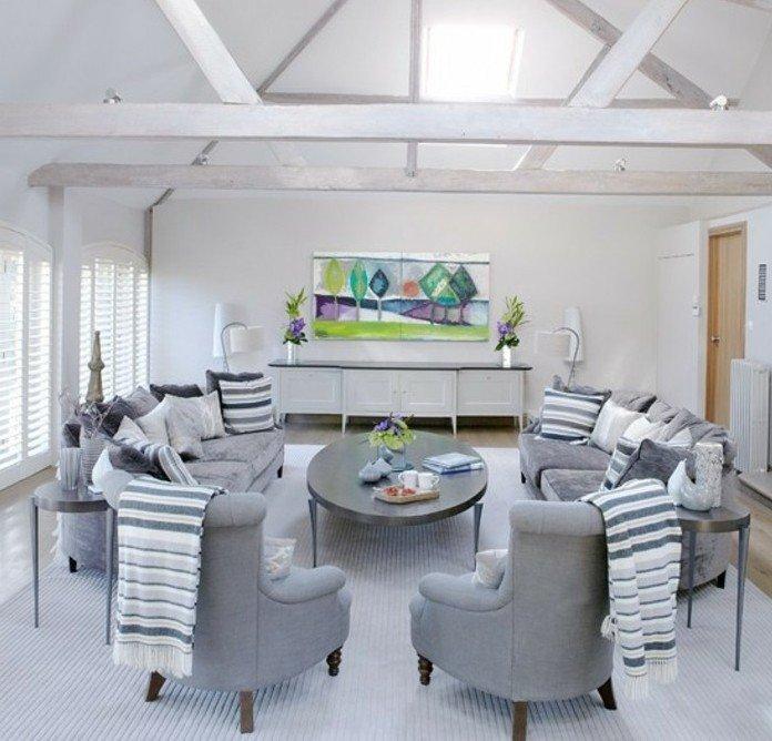 graue Sessel und graue Sofas, ein grauer Tisch und ein buntes Bild, eine Dachwohnung mit weißer Wandfarbe, Wohnzimmer Grau Weiß