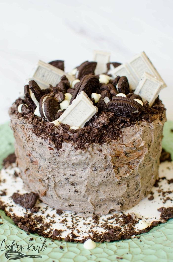 Milchcreme mit Oreo Krümmeln, verschiedene Riegel von weißer Schokolade, Oreo Kekse und Nüsse als Dekoration