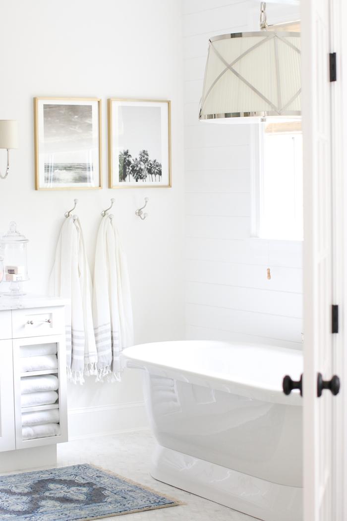 kleines weißes badezimmer mit einer weißen freistehenden badewanne und weißen tüchern, weiße badezimmer bilder, kleine madezimmer bilder