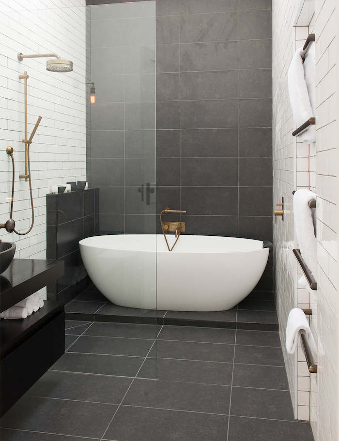 kleine badezimmer bilder, eine kleine weiße freistehende badewanne im badezimmer mit schwarzen und weißen wänden mit badezimmer fliesen und eine dusche und weiße tücher