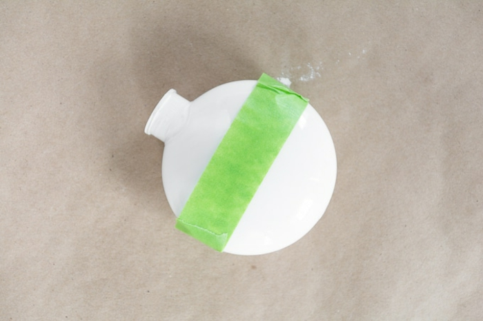 Weihnachtskugeln basteln, eine weiße Kugel als Vorlage mit grünem Tesafilm beklebt, damit die Hälfte nicht gefärbt wird