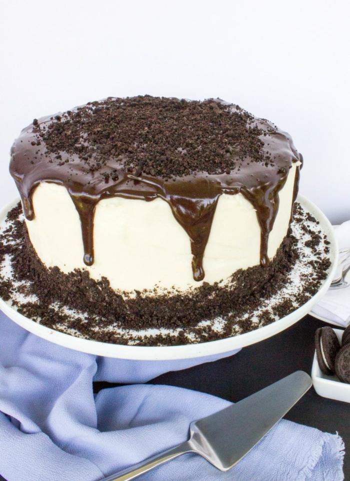 weiße Creme, Schokoladentopping, Oreo Kuchen mit Oreo Streuseln, mit blauem Tuch umgeben