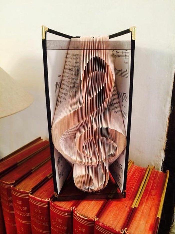 ein Violinschlüssel aus einem alten Musikbuch, Buchseiten falten, mit schwarzen Schleifen befestigen