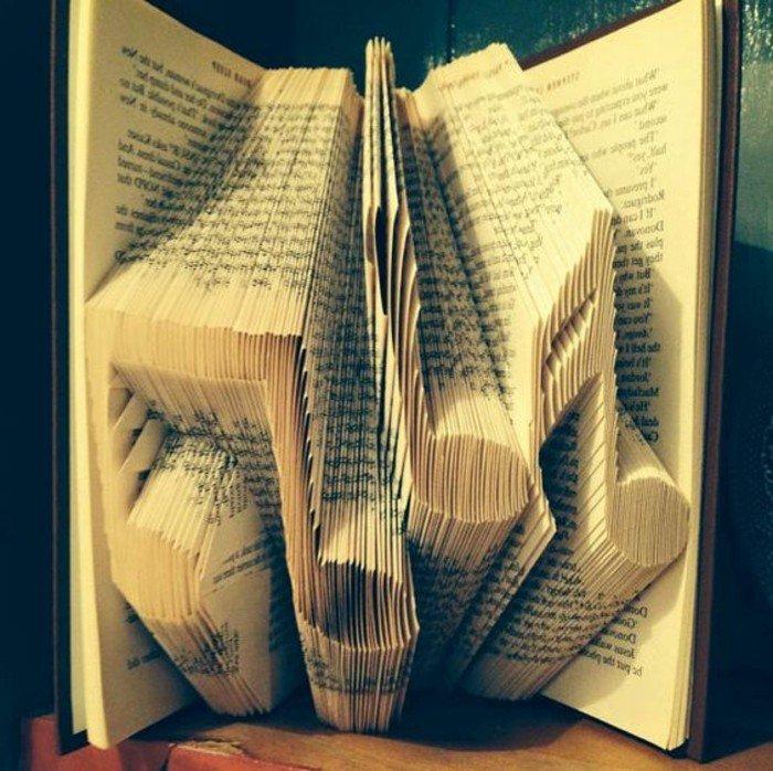 einige Noten in einem Origami Buch, schwarzer Buchumschlag, schlaue Technik