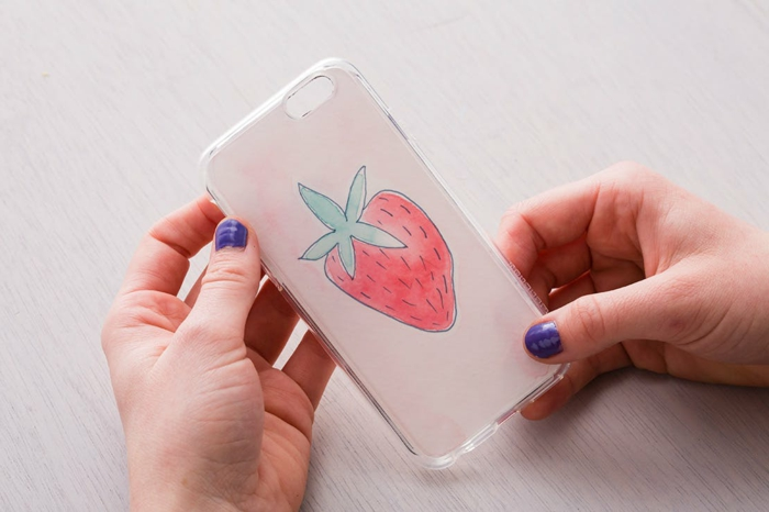 Handyhülle personalisieren, Bild von einer Erdbeere, Hand mit lila Nagellack, Hand hält Hülle