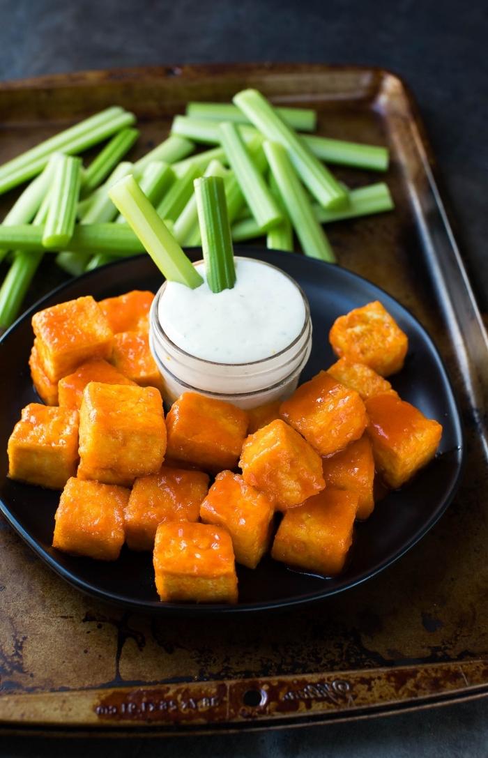 essen für gäste, tofu häppchen mit weißer soße, schwarzer runder teller, vorspeise