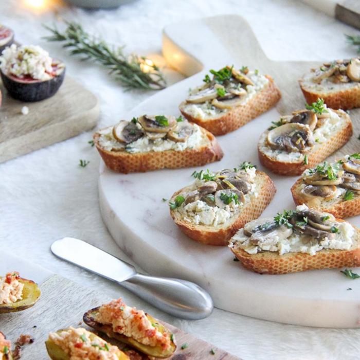 platte aus marmor, brotscheiben mit pilzen und käse, essen für geburtstag, gericht