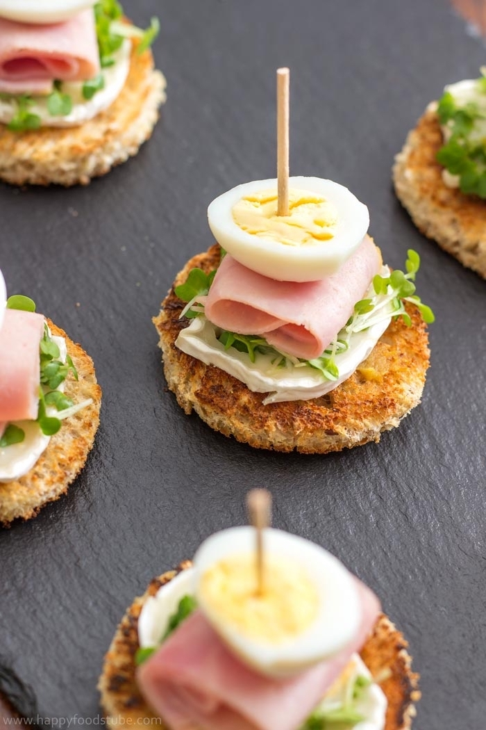 essen für party, gegrillte brottscheiben mit weißem käse, schinken und eiern, zahnstocher