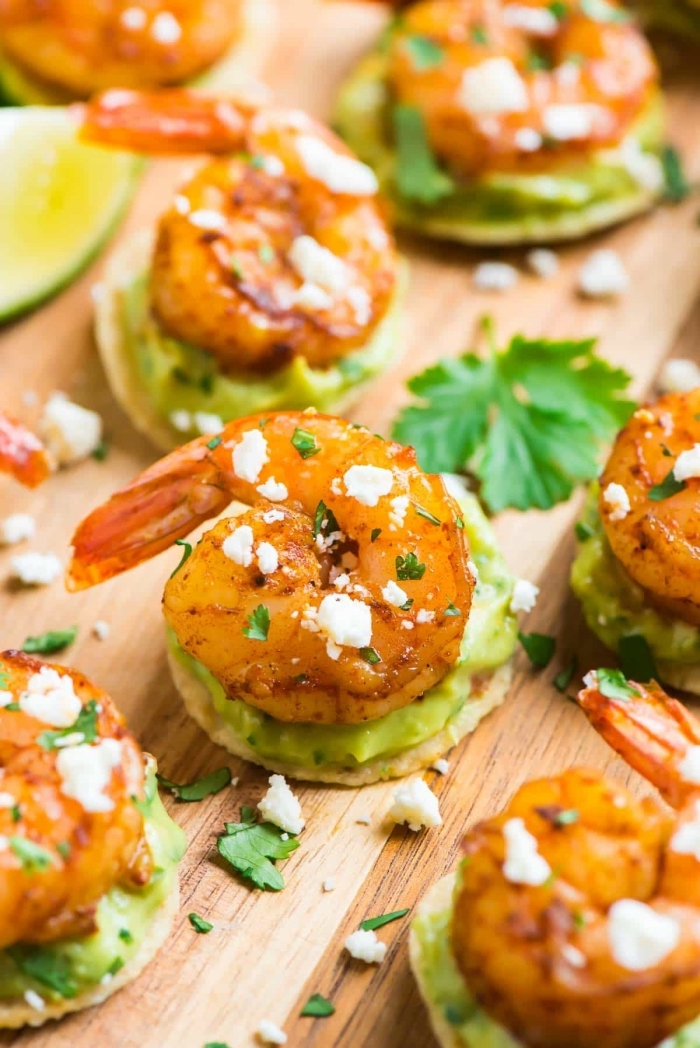 essen für party, cracker mit avocadopüree und garnelen, gehackte petersilie