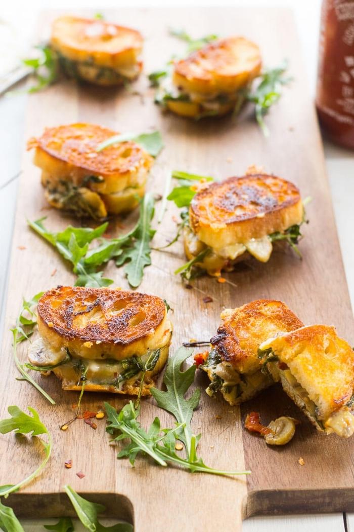 essen für party, sandwiches mit gemüse und käse, kleine brotscheiben, holzplatte