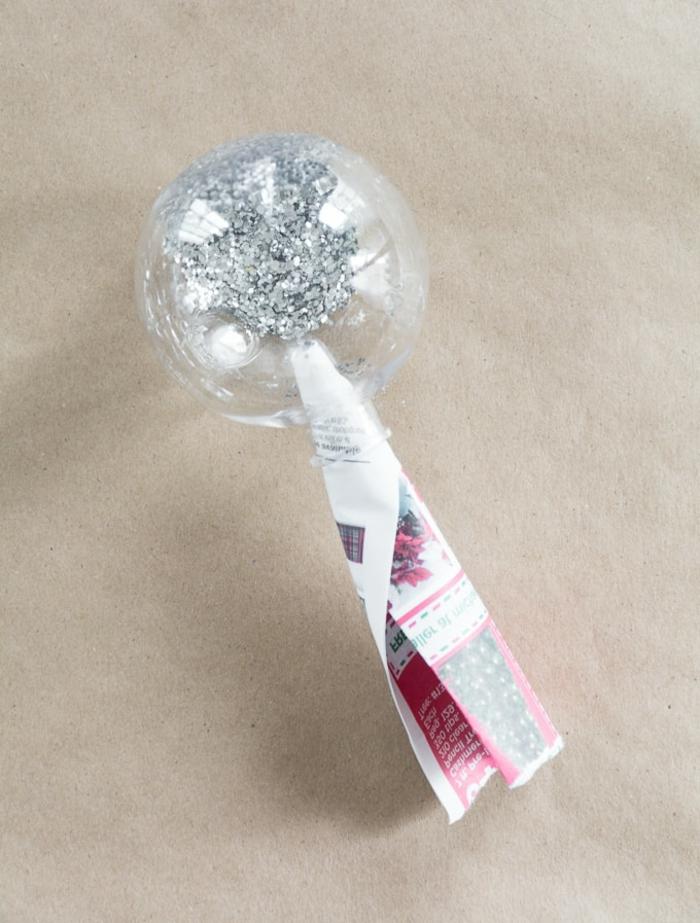 ein Trichter von Zeitungspapier hilft dabei, dass Sie Weihnachtskugeln selber machen und mit Glitter befüllen