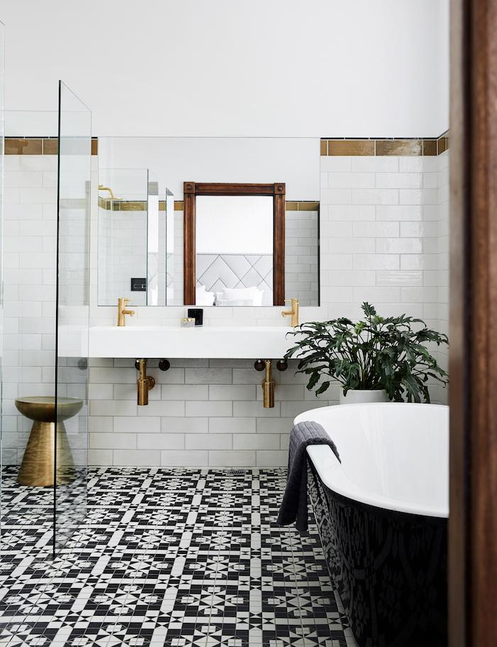 boden mit schwarzen und weißen badezimmer fliesen und eine schwarze freistehende badewanne, weißes waschbecken und regal