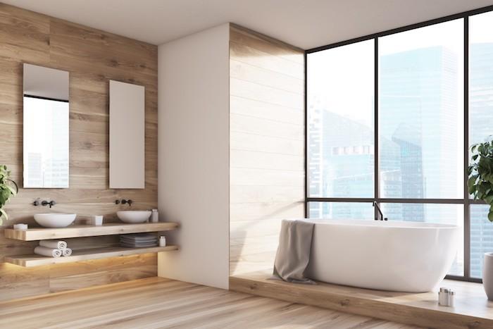 eine weiße freistehende badewanne und beige tücher, spiegel und weißes waschbecken. badezimmer mit fenstern