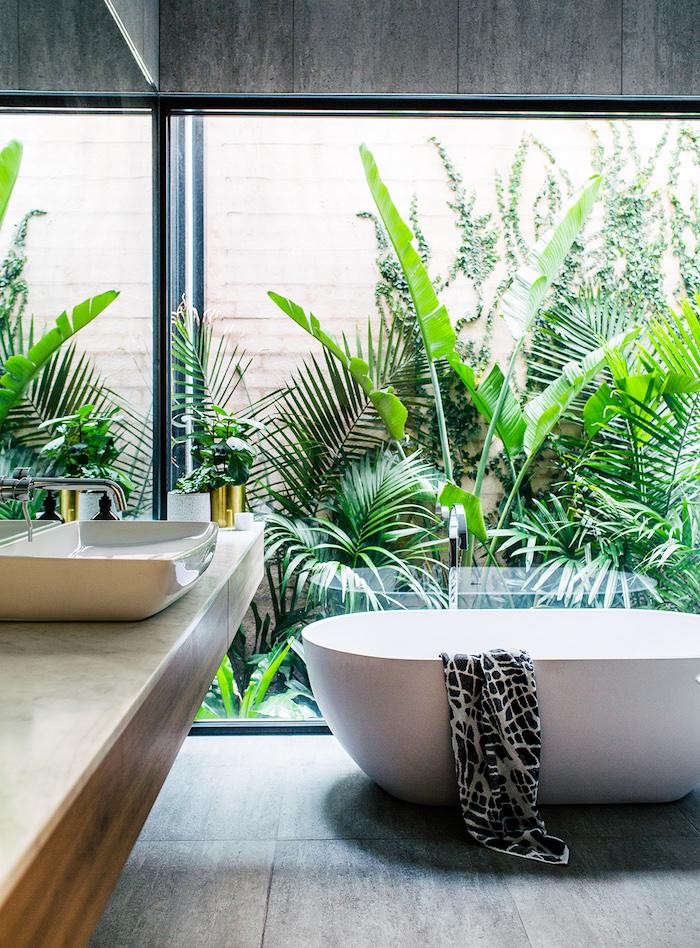 ein badezimmer mit einer weißen freistehenden badewanne, waschbecken aus holz, ein garten mit vielen grünen pflanzen und palmen