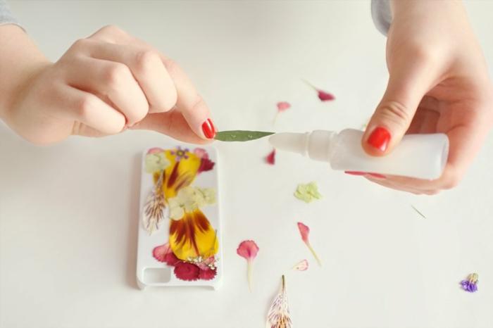 Grünes Blatt auf Handyhülle mit Klebstoff aufkleben, Hülle selbst gestalten, gepresste Blumen in rot und gelb auf Hülle