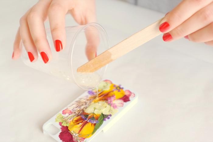 Weiße Hülle mit gepressten Blumen mit Harz bedecken, Hand mit rotem Nagellack, Handyhülle selber gestalten,